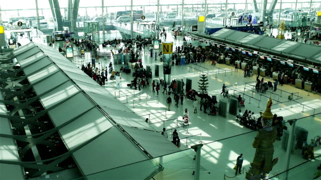 crowd of travelers at airport terminal check-in area - airline check in attendant stock videos and b-roll footage