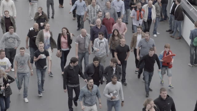 crowd of unidentified people walking down elevated olympic way sidewalk towards unseen wembley stadium - marciapiede video stock e b–roll