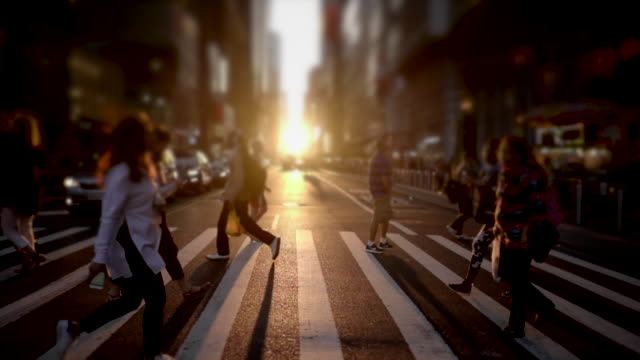vídeos de stock, filmes e b-roll de crowd of unrecognizable people walking in the city at sunset light. pedestrians crossing street. urban metropolis background - perspectiva espacial