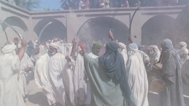 ws pan reenactment crowd of victorious middle eastern men returning to village waving swords and celebrating after battle while women pray nearby / iran - see other clips from this shoot 1007 stock videos & royalty-free footage
