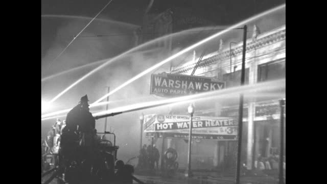 crowd of well-dressed men and women gathered at night in front of building on fire, streams of water from water cannons visible / closer view of... - 放水砲点の映像素材/bロール