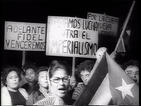 vídeos y material grabado en eventos de stock de crowd of women carry muerte al invasor poster in demonstration / crowd of women shouting and clapping singing and carrying posters as they walk in... - 1962