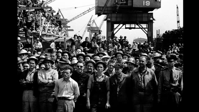 Crowd of workers on a dock at a shipyard standing facing camera Crowd of workers at a shipyard on January 01 1940