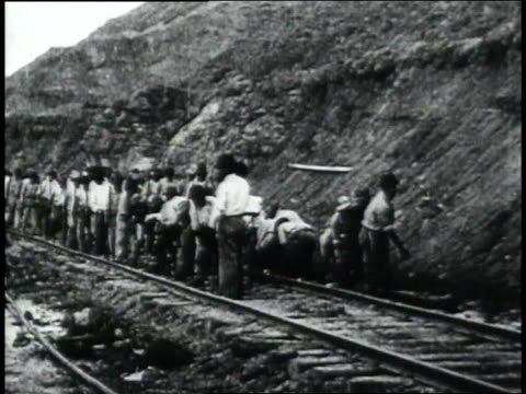 ws crowd of workers working on the railroad tracks at the bottom of a hill / republic of panama - 1906 stock-videos und b-roll-filmmaterial