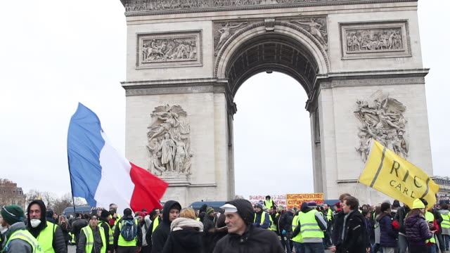 crowd of yellow vests in front of the triumphal arch with a flag where is written RIC