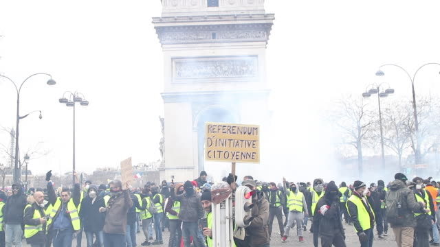 crowd of yellow vests in front of the triumphal arch with a sign where is written RIC