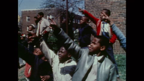 vidéos et rushes de crowd of young boys point at the flames and smoke of a nearby building fire - 1968