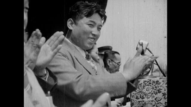 / crowd of young koreans listening to a speech / parade full of banners and signs / everyone dressed alike / kim il sung waves to the gathered crowd... - 1947年点の映像素材/bロール