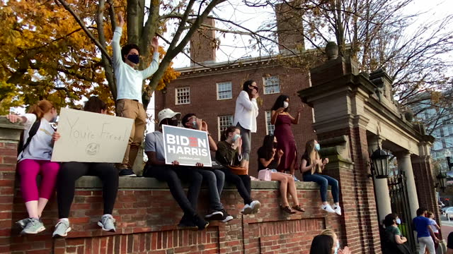 crowd of young people sit on a wall surrounding harvard yard, cheering as part of a demonstration of joy and relief after election results were... - surrounding wall点の映像素材/bロール