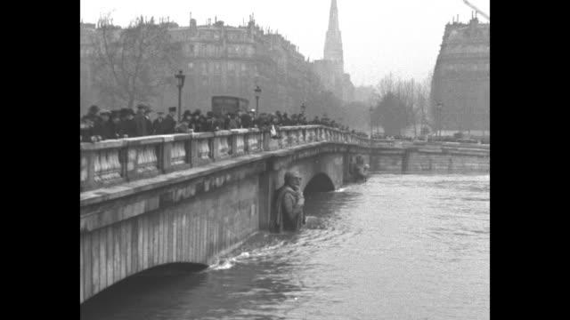 crowd on alma bridge watches flood waters / french zouave statue near arch of bridge halfway submerged / water rushing through bridge arch - 1920~1929年点の映像素材/bロール