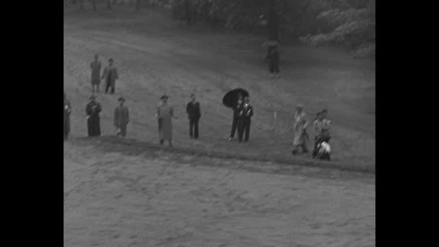 crowd on field watching gene sarazen hit ball / large crowd following players along shoreline of lake in rain / crowd members under umbrellas... - pgaイベント点の映像素材/bロール