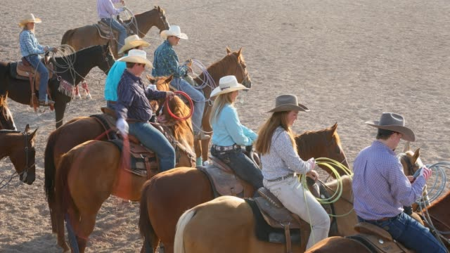 crowd on horseback watch the team roping event at a dusty rodeo - rodeo stock videos & royalty-free footage