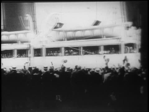 vídeos y material grabado en eventos de stock de b/w 1928 rear view crowd on shore waving as ocean liner passes in background / newsreel - 1928