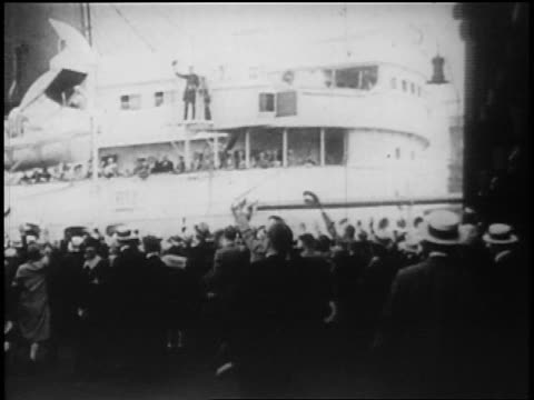 b/w 1928 rear view crowd on shore waving as ocean liner passes in background / newsreel - 1928 stock videos & royalty-free footage