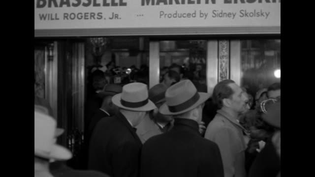 Crowd on sidewalk outside the Paramount Theater at the premiere of The Eddie Cantor Story mostly men wearing hats