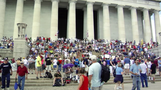crowd on steps of lincoln memorial people holding american flags sitting and walking / washington dc usa / audio - リンカーン記念館点の映像素材/bロール