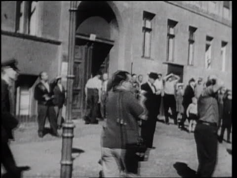 stockvideo's en b-roll-footage met b/w 1961 crowd on street watching people escape from east berlin / germany / newsreel - ontsnappen