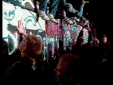 crowd on top of wall celebrating opening of berlin wall 09 nov 89 - bbc archive stock-videos und b-roll-filmmaterial