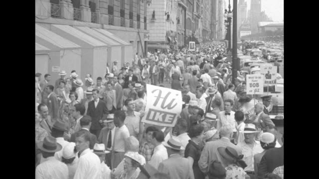 vidéos et rushes de vs crowd packed on sidewalk some holding up signs and posters street traffic to side / candidate senator robert taft at podium / he waves camera... - robert conrad