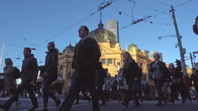 crowd people crossing road at flinders street station, melbourne - victoria australia stock videos & royalty-free footage