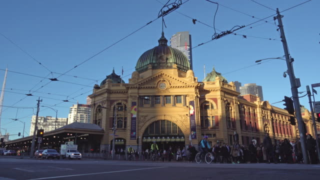 crowd people crossing road at flinders street station, melbourne - road sign stock videos & royalty-free footage
