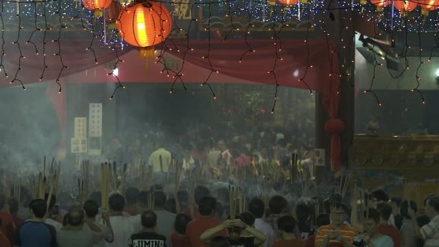 4K: Crowd People pray by using incense in temple during Chinese New Year.It is Chinese traditional custom.