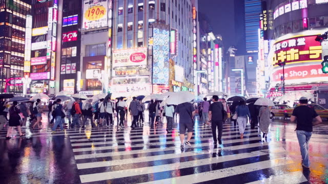Menge Menschen zu Fuß und beim Überqueren der Straße in der Stadt bei Regen