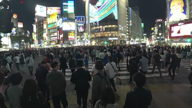 menge leute zu fuß auf shibuya kreuzung straße in der nacht in tokio, japan - besichtigung stock-videos und b-roll-filmmaterial