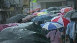 crowd people walking with umbrella during rainy season.