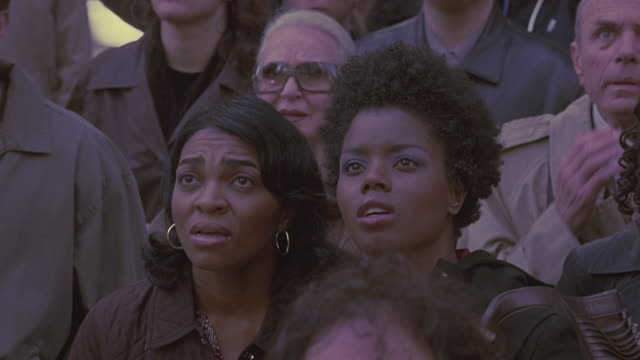 a crowd reacts in shock as they look up into the sky. - schockiert stock-videos und b-roll-filmmaterial