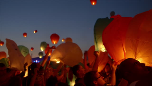 vídeos de stock, filmes e b-roll de cu crowd releasing lanterns for kupala night - festival tradicional