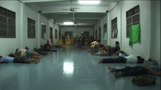 a crowd rests on a floor in a large room near golden buddhas. - ceiling fan stock videos & royalty-free footage