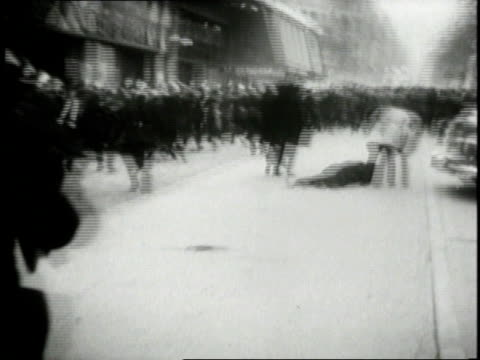 crowd rioting and police trying to control the riot / people running and a man lying on the street / police officer beating a rioter with a baton /... - 死傷者点の映像素材/bロール