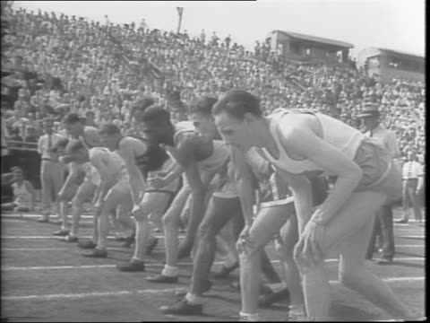 Crowd rises to their feet to watch the 5000 meter run / the gun fires and the men in the 5000 meter take off / overhead shot of the race / Gunder...