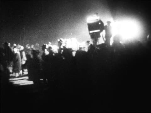 b/w 1927 crowd running by searchlight to greet lindbergh at le bourget airfield at night / paris - 1927 stock videos & royalty-free footage