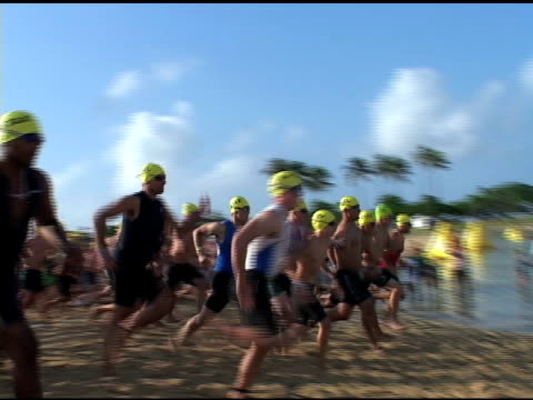 crowd runs into water at the start of the 2009 honolulu triathlon crowd run into water at start of honolulu tri on january 01 2010 - salmini stock videos and b-roll footage