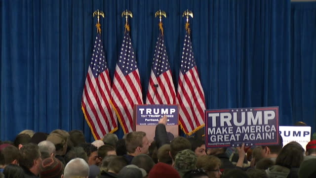 """crowd seen in front of an empty podium with 4 american flags behind it at a 2016 trump rally in portland, maine. blue sign seen """"trump make american... - 2016 united states presidential election stock videos & royalty-free footage"""