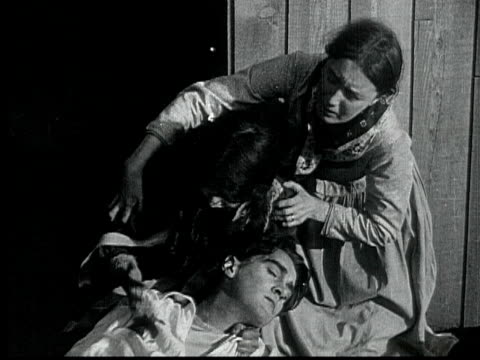 1916 b/w montage ms ws ha crowd shooting and setting church on fire, two women rescuing wounded man, 1880s / santa monica, california, usa - mob stock-videos und b-roll-filmmaterial