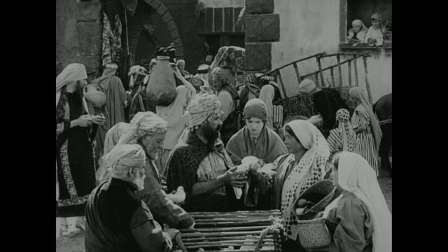 a crowd shops at a busy market in biblical times - anno 1916 video stock e b–roll