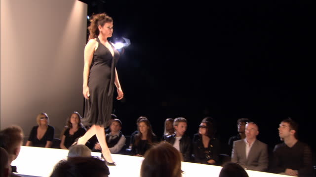 ms crowd sitting around catwalk at fashion show/ tu ms pan model in black dress walking on catwalk/ zi model/ london, england - hourglass stock videos & royalty-free footage