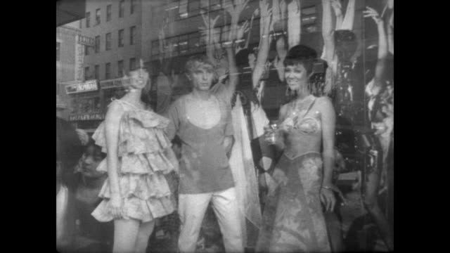 Crowd stand outside New York department store / live models pose at a cocktail party theme in front window / models all wearing paper clothes / CU...