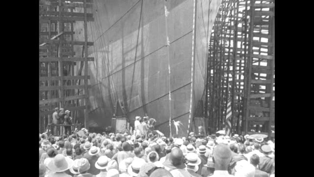 ws crowd standing in front of prow of ship in dry dock and platform next to prow / very qs title card anne thomas breaks bottle of over bow / 11yo... - ship's bow stock videos & royalty-free footage