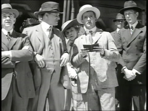 crowd standing outside looking at draft lottery bulletin board men in crowd talking to each other about number being pulled one male in boater hat... - 1917 stock videos & royalty-free footage