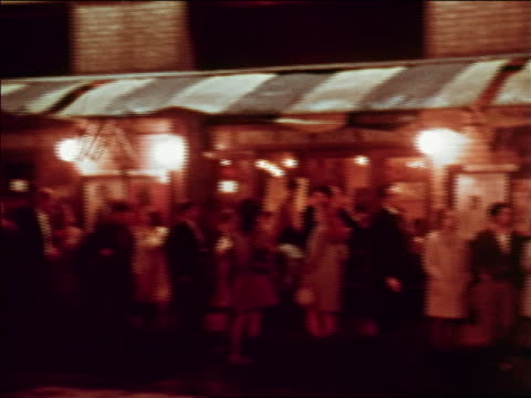 1969 pan crowd standing under awning on city sidewalk at night / greenwich village, nyc - anno 1969 video stock e b–roll