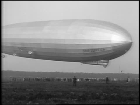 B/W 1929 crowd standing under Graf Zeppelin as it descends in field / Lakehurst, NJ / newsreel