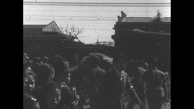 crowd stands about near two wrecked trains after their collision in osaka / cu smashed ends of both trains / vs wrecked trains and smashed ends of... - 1940~1949年点の映像素材/bロール
