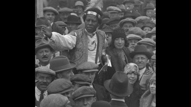 crowd stands and mills around near horses / racetrack tout speaks about the race / crowd places bets with bookies' banners and signs visible / horses... - 1930 stock videos & royalty-free footage