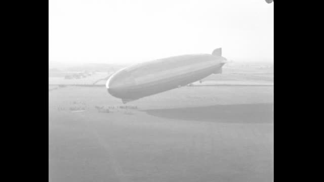 stockvideo's en b-roll-footage met ws crowd stands on airfield as graf zeppelin descends releasing steam and dropping item to ground / ws zeppelin with nose approaching ground /... - 1933