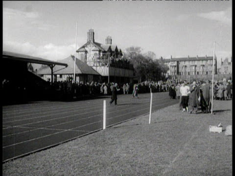 crowd surrounding athletics race track and on balcony of club house to watch roger bannister break the 4 minute mile iffley road oxford 6 may 1954 - マイル点の映像素材/bロール