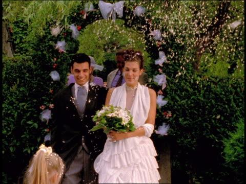 vídeos de stock e filmes b-roll de ms crowd throwing confetti on bride + groom as they walk through flowery arch outdoors / parents background - pai da noiva